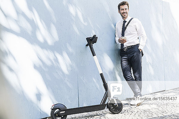 Entspannter junger Geschäftsmann mit Handy und E-Scooter an einer Wand lehnend