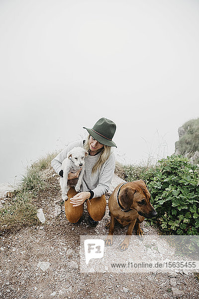 Young woman with two dogs on viewpoint