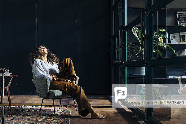 Young businesswoman relaxing in loft office