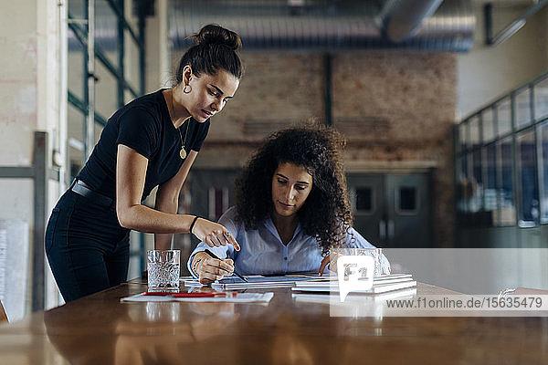 Zwei junge Geschäftsfrauen unterhalten sich am Konferenztisch im Loft-Büro