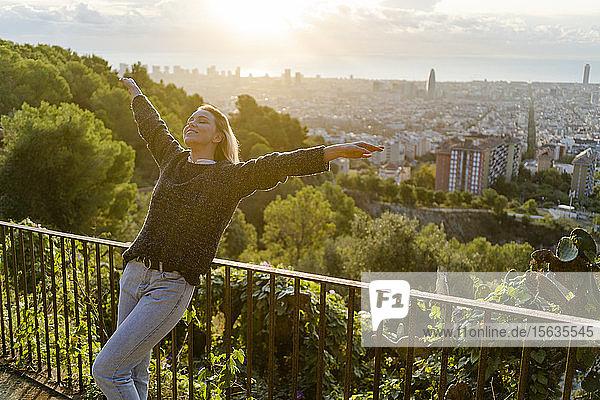 Unbeschwerte junge Frau steht bei Sonnenaufgang über der Stadt  Barcelona  Spanien
