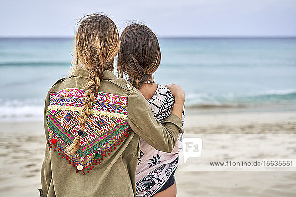 Rückansicht von zwei jungen Frauen,  die nahe beieinander an einem Strand stehen