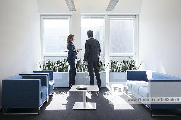 Geschäftsfrau und Geschäftsmann schauen aus dem Fenster in der Büro-Lounge