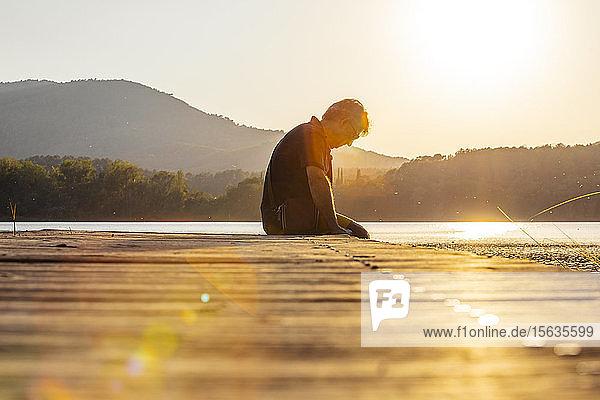 Älterer Mann sitzt auf einem Holzsteg und schaut nach unten  gegen die Sonne
