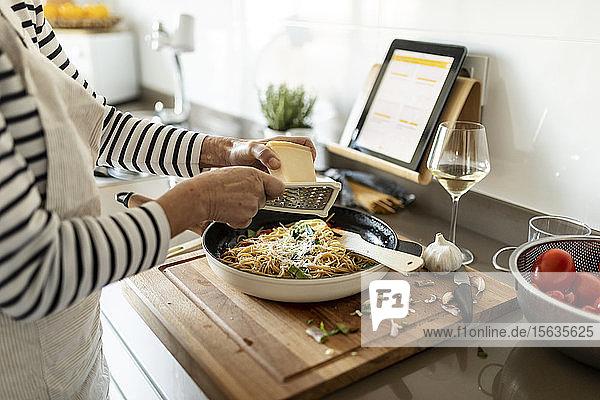 Nahaufnahme einer Frau mit Tablette beim Kochen von Nudelgerichten in der heimischen Küche