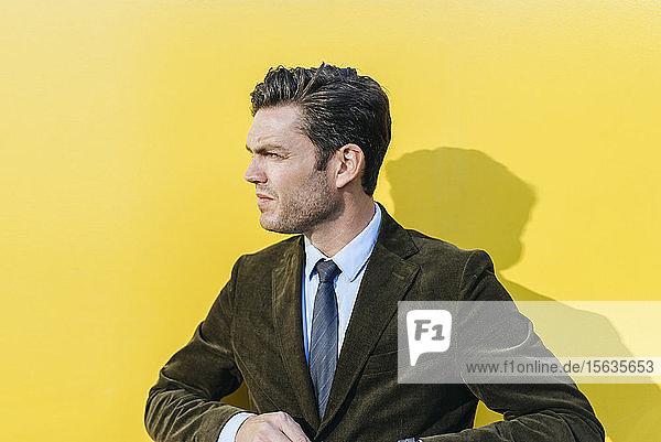 Porträt eines Geschäftsmannes vor gelber Wand