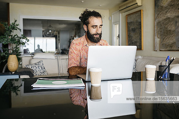 Man working on table at home using laptop