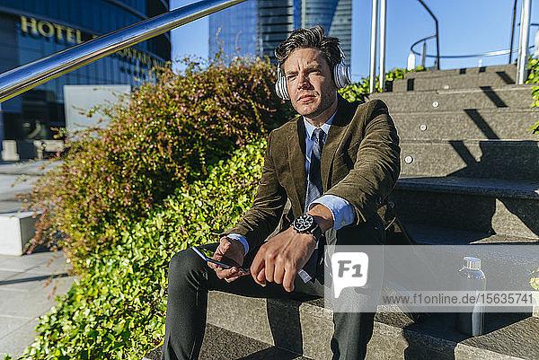 Geschäftsmann mit Kopfhörern und Smartphone bei einer Pause im städtischen Geschäftsviertel  Madrid  Spanien