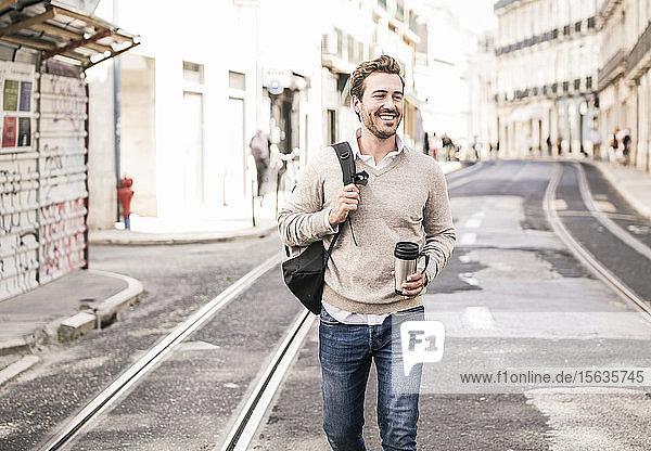 Lächelnder junger Mann mit Rucksack und Kaffeetasse in der Stadt unterwegs  Lissabon  Portugal