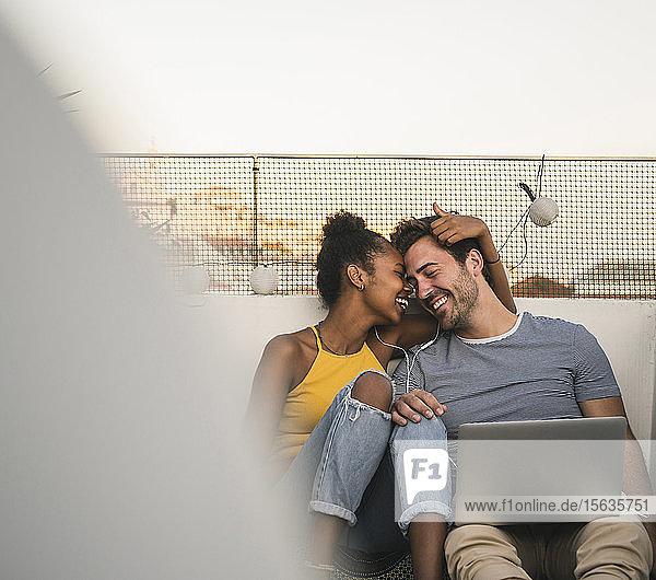 Glückliches junges Paar mit Laptop und Kopfhörern sitzt abends auf dem Dach