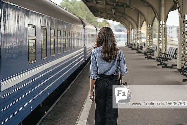 Rear view of young female traveller walking on the platform