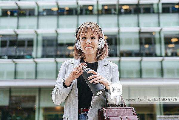 Porträt einer lächelnden Frau mit Kopfhörer  die eine wiederverwendbare Flasche in der Stadt öffnet
