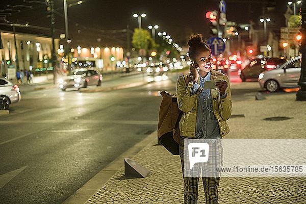 Porträt einer lächelnden jungen Frau mit Kopfhörer und Smartphone in der Stadt bei Nacht  Lissabon  Portugal
