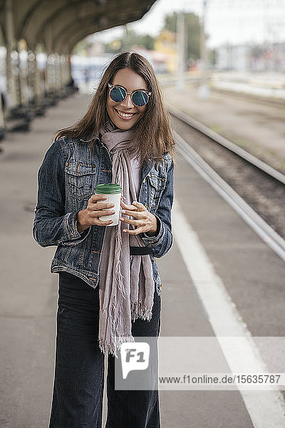 Young smiling traveller with coffee to go on train station