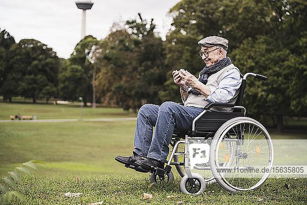 Glücklicher älterer Mann sitzt im Rollstuhl auf einer Wiese und benutzt ein Smartphone