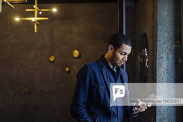 Junger Mann in stilvollem Büro  mit Smartphone Junger Mann in stilvollem Büro, mit Smartphone