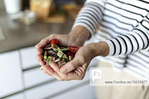 Nahaufnahme einer Frau  die zu Hause in der Küche kocht und gehacktes Gemüse hält