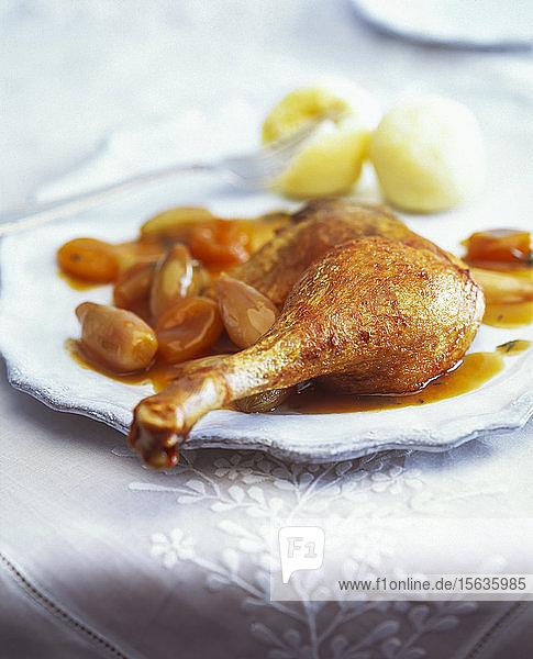 Nahaufnahme einer gebratenen Gänsekeule mit Aprikosen und Schalotten in einem Teller auf dem Tisch serviert