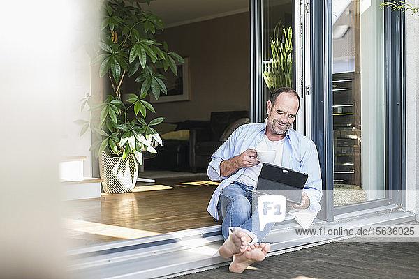 Lächelnder reifer Mann sitzt zu Hause an der Terrassentür mit Tablette und Kaffeetasse