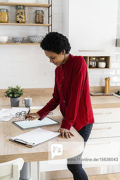 Junge Frau benutzt Grafiktablett zu Hause