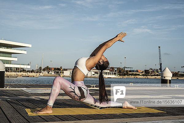Asiatische Frau  die auf einem Pier im Hafen Yoga praktiziert  Krieger-Pose Asiatische Frau, die auf einem Pier im Hafen Yoga praktiziert, Krieger-Pose