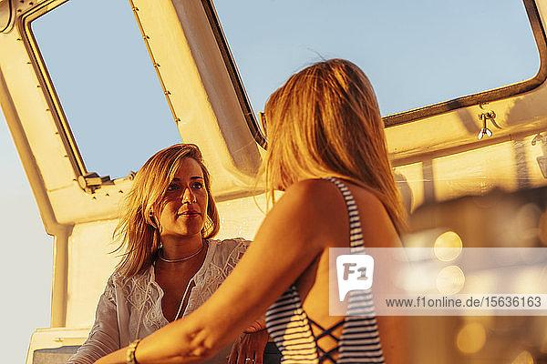 Freunde unterhalten sich während der Bootsfahrt im Abendlicht