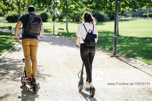Rückansicht eines Elektroroller fahrenden Paares in einem Stadtpark