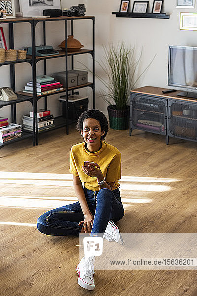 Portrait of smiling young woman sitting on the floor at home holding smartphone