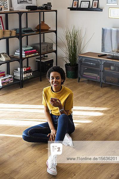 Porträt einer lächelnden jungen Frau,  die zu Hause auf dem Boden sitzt und ein Smartphone in der Hand hält