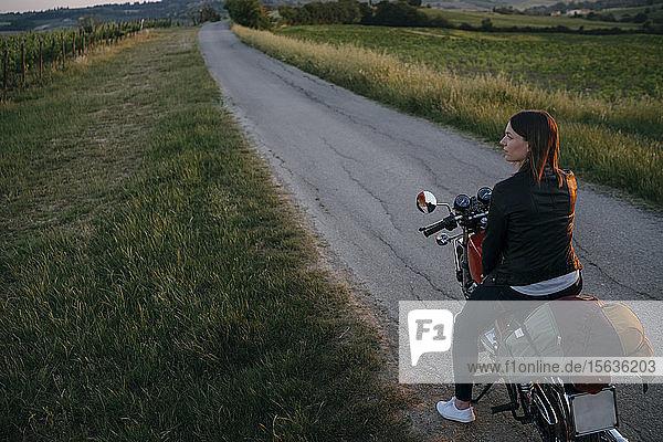 Junge Frau mit Oldtimer-Motorrad steht bei Sonnenuntergang auf der Landstraße und schaut auf die Aussicht  Toskana  Italien