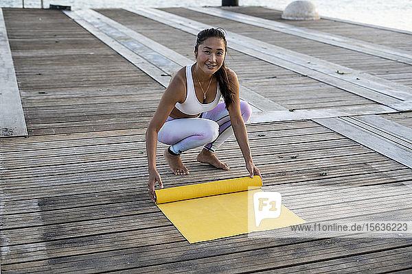 Asiatische Frau  die auf einem Pier im Hafen Yoga praktiziert und ihre gelbe Yogamatte ausrollt Asiatische Frau, die auf einem Pier im Hafen Yoga praktiziert und ihre gelbe Yogamatte ausrollt