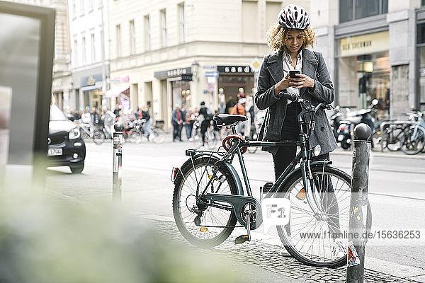 Frau mit Fahrrad und Smartphone in der Stadt  Berlin  Deutschland