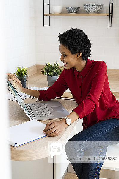 Smiling young woman using laptop at home