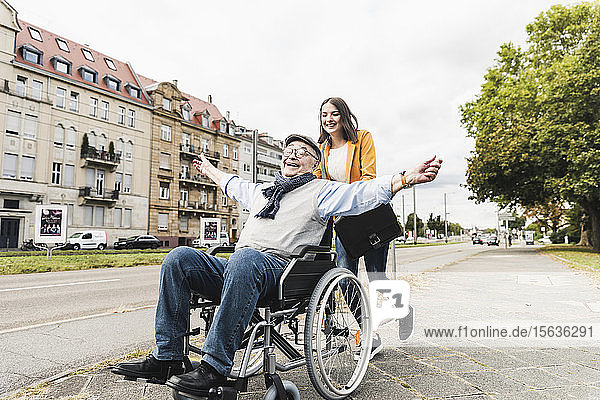 Smiling young woman pushing happy senior man in wheelchair