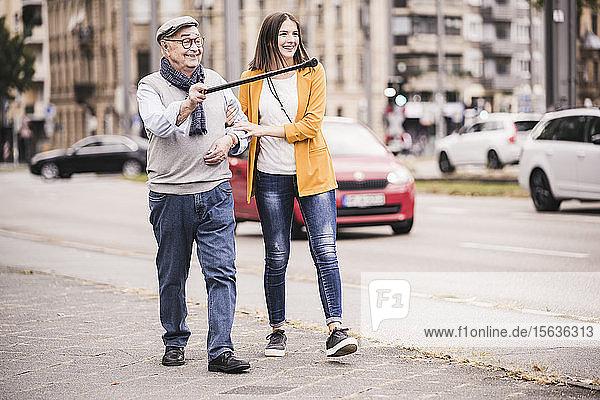 Adult granddaughter assisting her grandfather walking