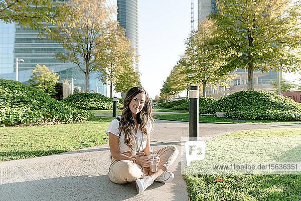 Junge Frau sitzt im Park  trinkt Milchshake und schaut in die Kamera