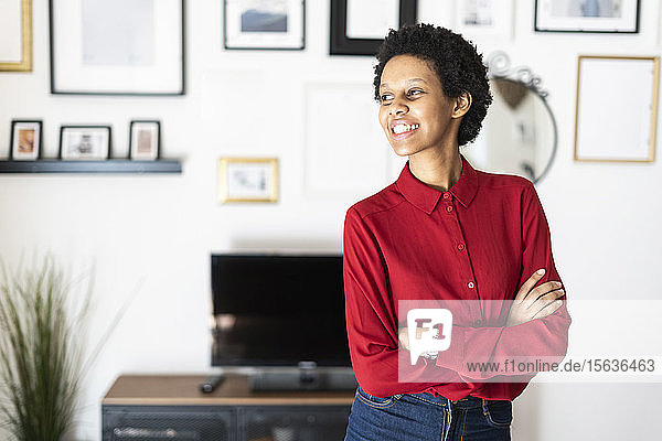 Smiling young woman at home looking sideways