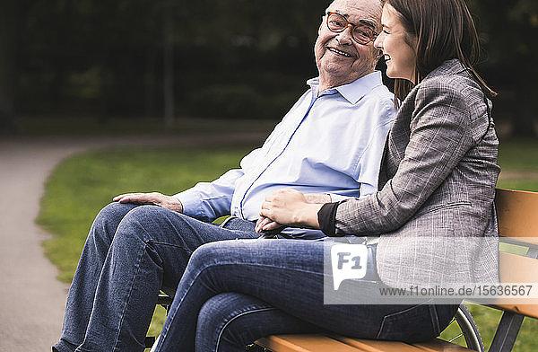 Älterer Mann und Enkelin entspannen gemeinsam auf einer Parkbank