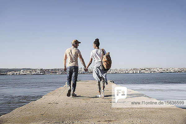 Young couple walking on pier at the waterfront  Lisbon  Portugal