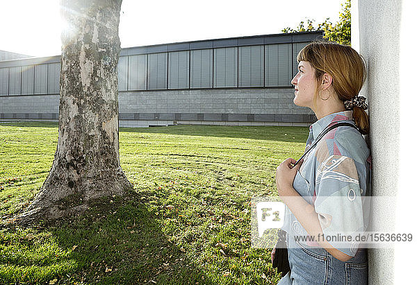 Smiling young woman leaning against wall enjoying sunlight