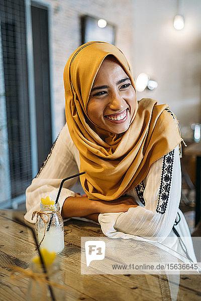 Junge muslimische Frau mit gelbem Hidschab in einem Café