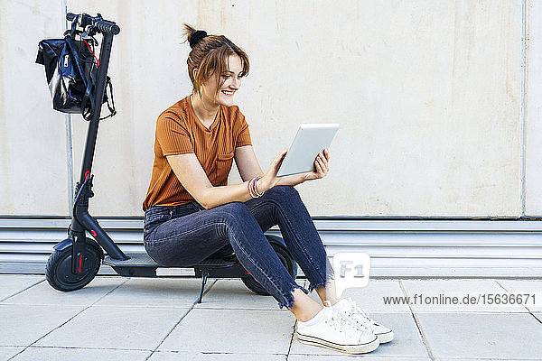 Portrait of smiling woman sitting on electric scooter using digital tablet