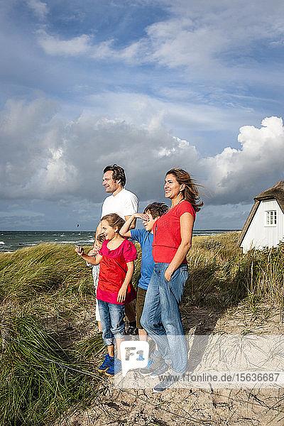 Glückliche Familie steht in einer Stranddüne und schaut auf Aussicht  Darss  Mecklenburg-Vorpommern  Deutschland