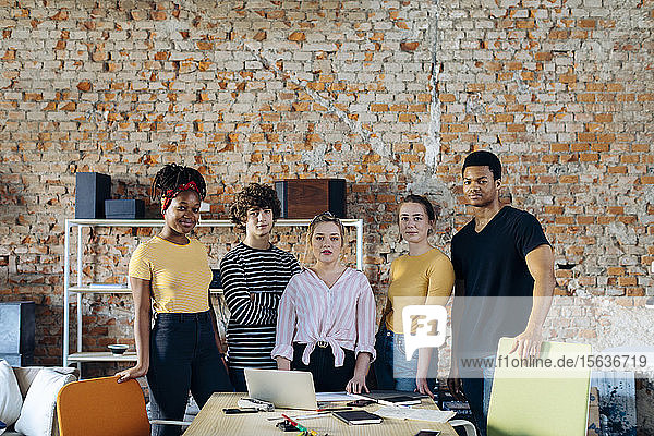 Portrait of confident young people at table in a loft