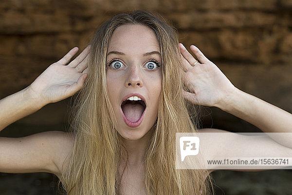 Porträt einer schreienden jungen Frau  die die Hände hebt