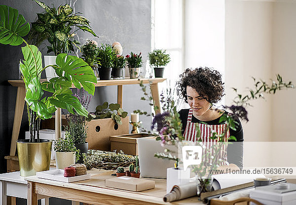 Young woman using laptop in a small shop with plants