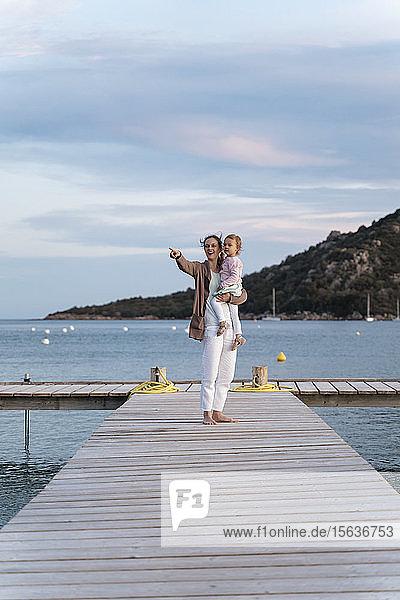 Happy mother carrying daughter on a jetty at sunset
