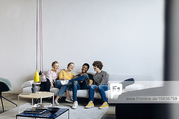 Happy young people sitting together on couch sharing smartphone