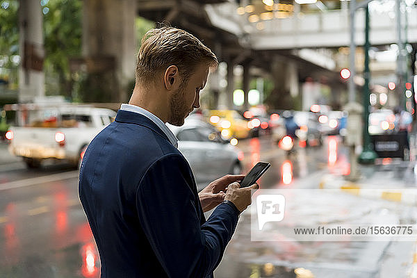 Young businessman using smartphone in Bangkok during a rainy day