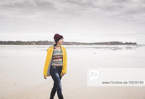 Young woman wearing yellow rain jacket at the beach  Bretagne  France